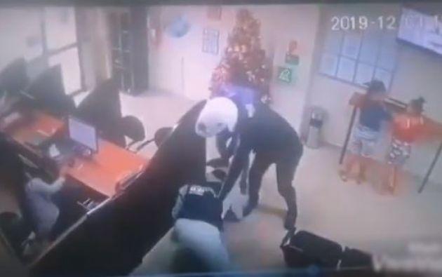 Un video de seguridad muestra el momento en el que los antisociales ingresan al banco y someten el guardia de seguridad. Foto: captura de video.