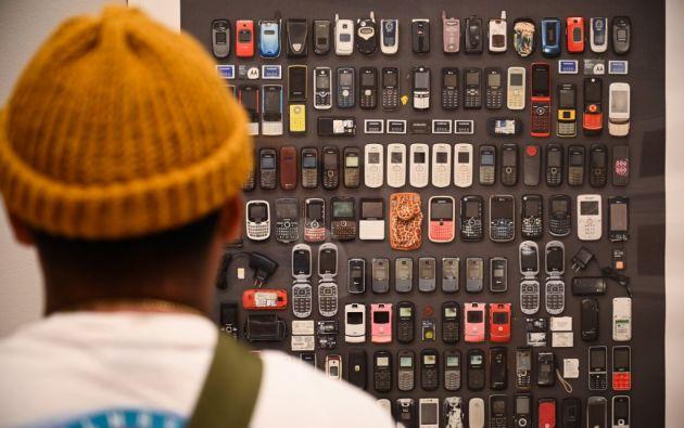 Teléfonos celulares, de distintos modelos y épocas, fueron confiscados a los migrantes. Ahora son obras de arte que cuestionan las políticas migratorias. Foto: AFP.