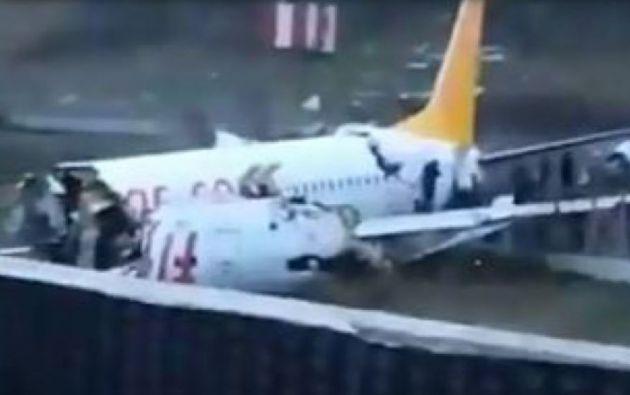 Pasajeros abandonan el avión por huecos en el fuselaje causados al romperse el aparato.