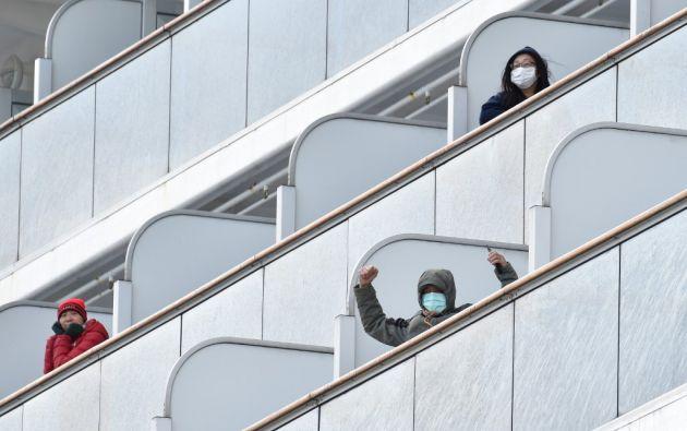Pasajeros del crucero Diamond Princess se asoman por los balcones, sin poder abandonar el barco. Foto: AFP