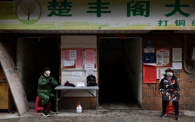 Ciudadana china sentada en la entrada de un edificio residencial en Wuhan. Foto: Reuters.