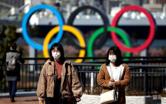Personas utilizando mascarillas frente a grandes aros olímpicos. Foto: Reuters.