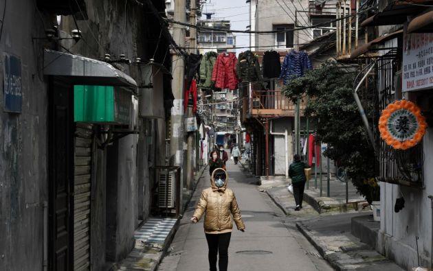 Mujer utilizando una mascarilla mientras camina por las calles de Wuhan. Foto: Reuters.