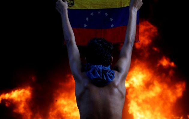 Hombre sostiene una bandera de Venezuela durante las protestas contra el presidente Nicolás Maduro. Foto: Reuters.