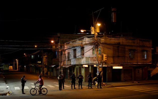 Un ciclista pasa por un puesto de control policial después de que el gobierno de Ecuador impuso un toque de queda nocturno para evitar la propagación del coronavirus. Foto: Reuters.