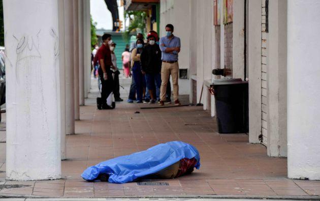 Este lunes el cadáver de un hombre yacía en una acera debajo de una sábana de plástico azul en el centro de Guayaquil. Foto: Reuters.