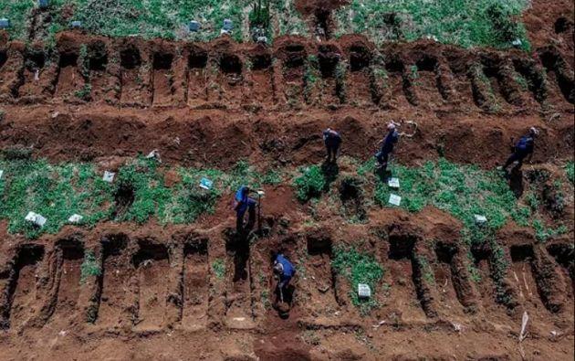 Empleados del cementerio preparan tumbas para los fallecidos por coronavirus. Foto: AFP