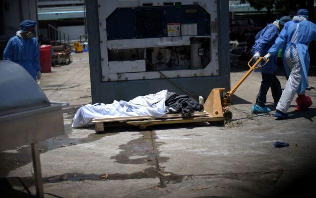 Los trabajadores de la salud que usan equipo de protección llevan un cadáver a un contenedor refrigerado afuera del Hospital Teodoro Maldonado Carbo. Foto: Reuters.