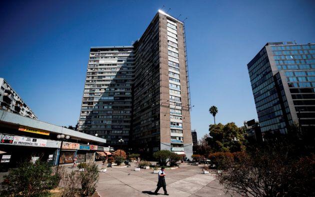 Un hombre camina frente a un edificio de viviendas en la comuna de Providencia en Santiago (Chile). Foto: EFE.