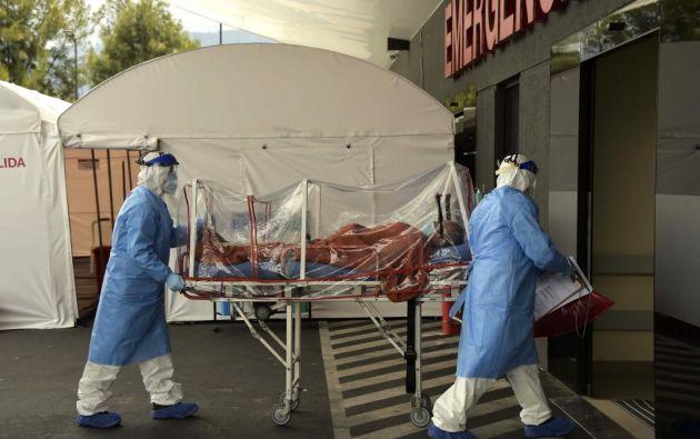 Médicos trasladan a paciente contagiado de COVID-19 en el Hospital IESS Sur de Quito. (AFP)