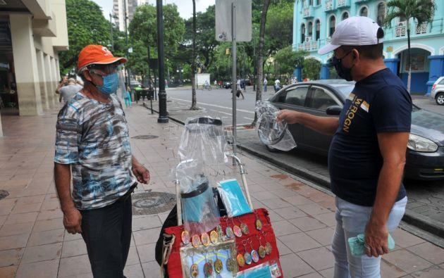 Aunque Guayaquil se mantiene con el semáforo en rojo, las ventas ambulantes están presentes en varias calles de la ciudad. Foto: AFP.