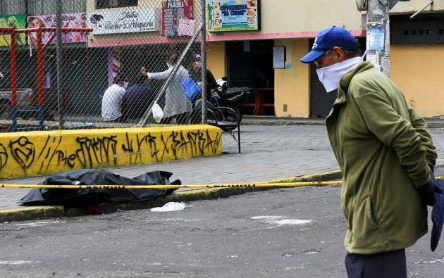 Policía con trajes especiales y personal sanitario asisten a una persona que yace en el piso, tras desplomarse en una calle de Quito. Foto: EFE.