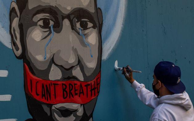 Un artista urbano pinta un mural en Los Angeles en honor a George Floyd. Foto: AFP.
