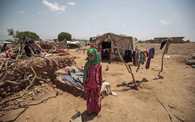 Una niña yemení desplazada internamente de pie fuera de su tienda. Foto: FAO.