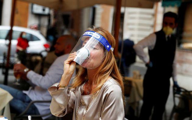 Una mujer con una máscara toma un café en un bar de Roma tras el levantamiento de las restricciones en mayo.