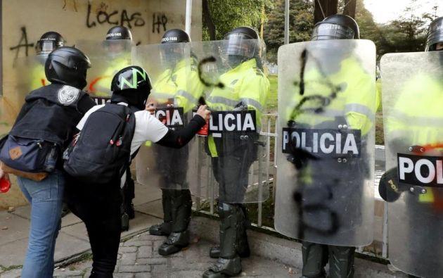 Manifestantes pintan los escudos de la policía colombiana. EFE