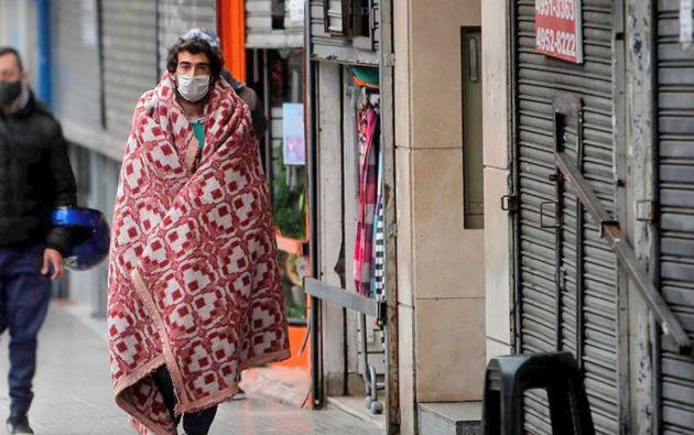 Transeúntes caminan usando mascarillas para protegerse del virus en Buenos Aires, Argentina. Foto: EFE