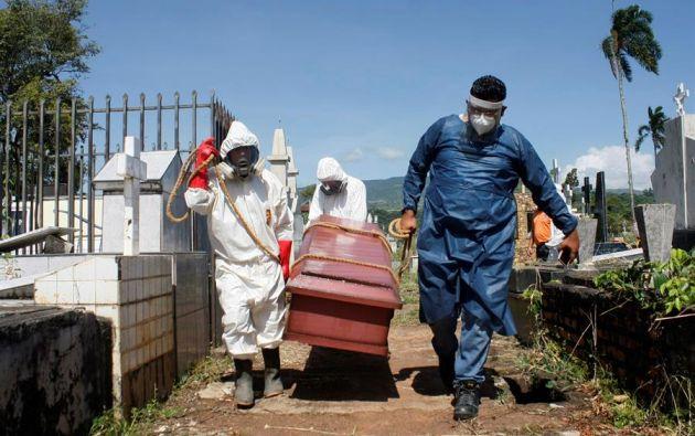 Trabajadores gubernamentales llevan un ataúd con una víctima de covid-19 para enterrarlo. Foto: EFE.
