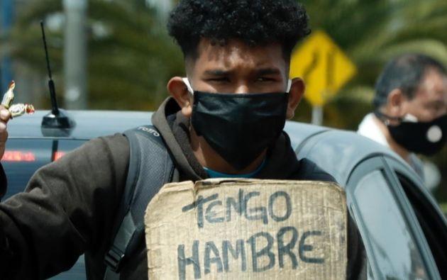 Un hombre vende dulces y pide ayuda en un semáforo en Bogotá, Colombia. Foto: EFE