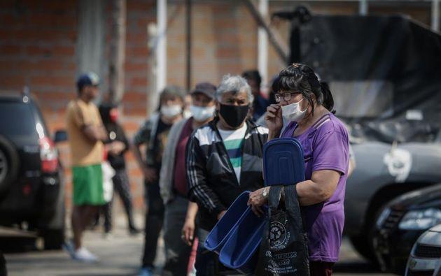 Personas usan tapabocas hoy mientras hacen fila para obtener alimentos en un comedor comunitario, en una villa de la Ciudad de Buenos Aires. Foto: EFE