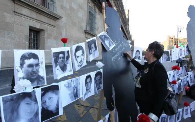 Una mujer escribe en una silueta junto a fotografías de personas desaparecidas en las afueras del Palacio Nacional, en Ciudad de México, México. Foto: EFE