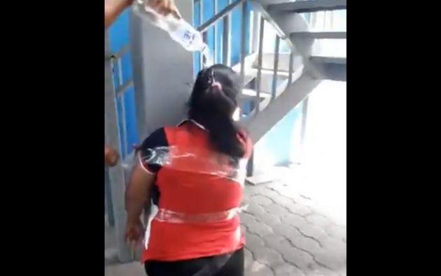 En las imágenes se ve a una mujer atada con cinta a un pilar y que de pronto es agredida por una agente municipal del cantón Durán.