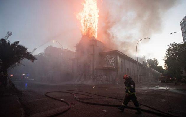 Un grupo de bomberos trabaja en la extinción del incendio de la parroquia de la Asunción en los alrededores de la Plaza Italia de Santiago (Chile). Foto: EFE.
