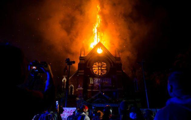 Un grupo de manifestantes observa como arde la iglesia de San Francisco de Borja, actualmente destinada al servicio religioso de Carabineros de Chile. Foto: EFE