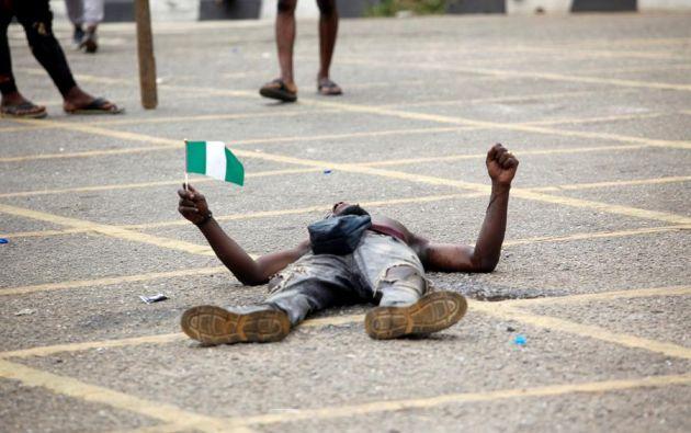 Un manifestante yace en el suelo con una bandera de Nigeria en protesta contra la brutalidad policial que vivió ese país este martes. Foto: EFE.