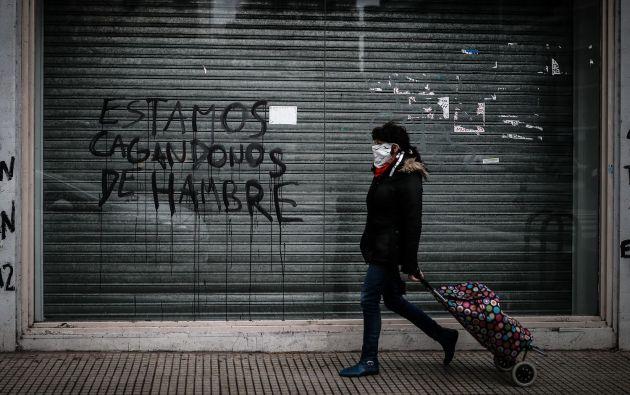 Una mujer pasa frente a un local de la ciudad de Buenos Aires cerrado a causa de la crisis económica.Foto: EFE