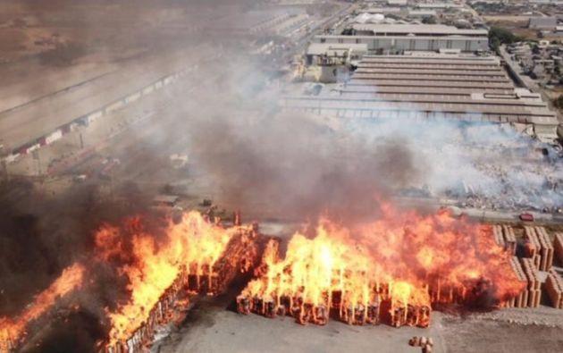 Los fuertes vientos que se han producido en la tarde reavivaron el fuego y continúa quemándose la materia prima de esa empresa. Los casacas rojas están en alerta para evitar que las chispas se trasladen a los barrios cercanos. Foto: @BomberosGYE.