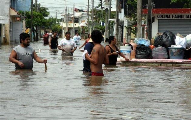 Varias personas caminan por una calle de la ciudad mexicana de Veracruz, inundada por las lluvias de un huracán. Foto: EFE