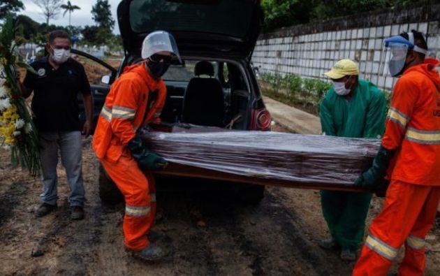 Trabajadores cargan el ataúd con el cuerpo de un fallecido por covid-19 en el área destinada a las víctimas de la pandemia en el cementerio público Nossa Senhora Aparecida, en Manaos, Amazonas (Brasil). Foto: EFE