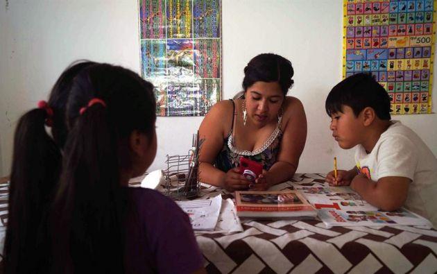 Una mujer acompaña a sus hijos para las tareas en clases. Foto: EFE