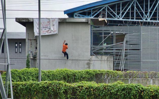 Un preso desciende por una pared luego de colgar un letrero en el que pide hablar con los medios de comunicación. Foto: EFE