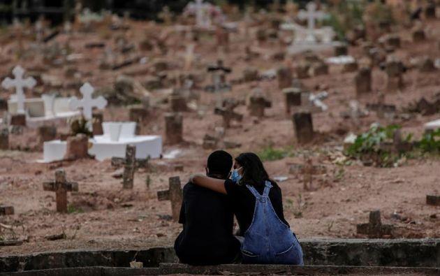 Una pareja llora a una mujer víctima de la covid-19 en un cementerio de Río de Janeiro. Foto: EFE/Antonio Lacerda