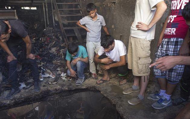 Una multitud observa el edificio en el que fueron asesinados los militantes de Hamás Marwan Qawasmeh y Amar Abu Aisha. Foto: EFE