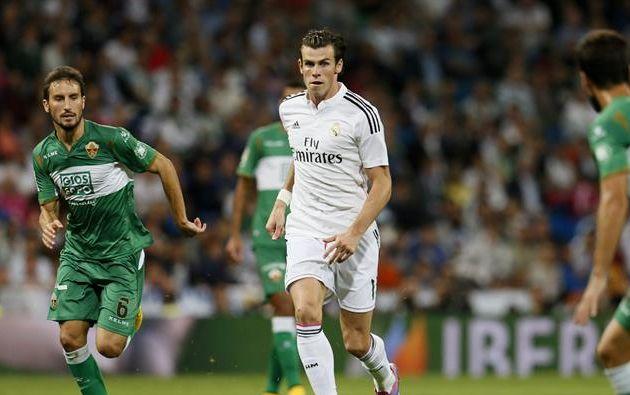 El delantero galés del Real Madrid Gareth Bale (c) controla el balón ante el los jugadores del Elche Pedro Mosquera (i) y Domingo Cisma durante el partido correspondiente a la quinta jornada de Liga que disputan esta noche en el estadio Santiago Bernabéu. Foto: EFE