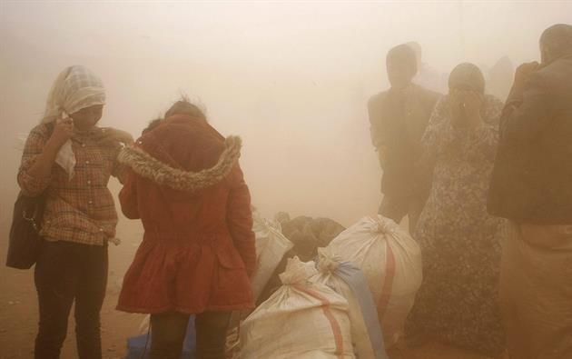 Refugiados sirios soportan una tormenta de arena mientras esperan en la frontera turco-siria cerca de Sanliurfa (Turquía) hoy, miércoles 24 de septiembre de 2014. Foto: EFE