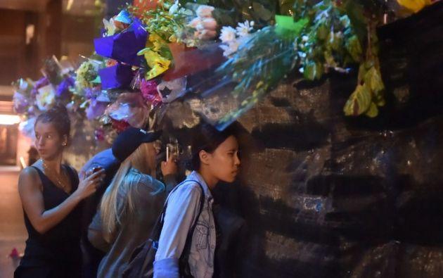 Una visitante mira a través de una barrera la escena del crimen. Foto: AFP