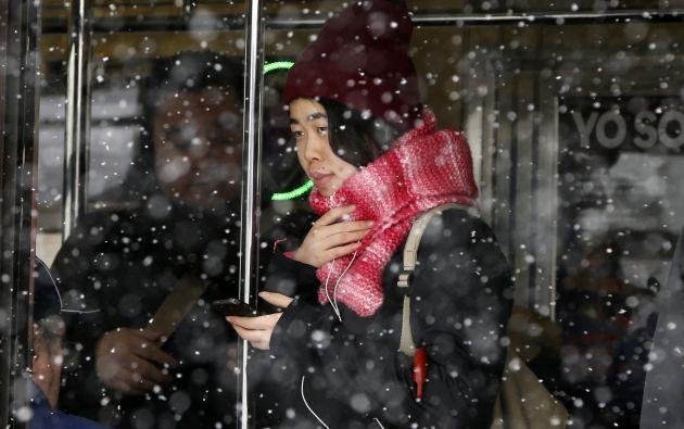 Una mujer dentro de una estación del metro en Queens.