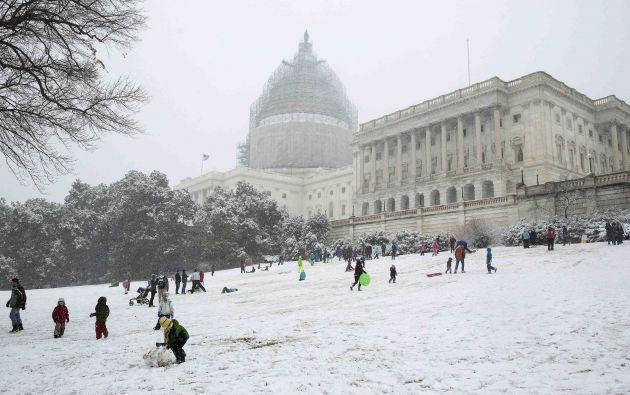 Niños y adultos juegan con la nieve fuera del Capitolio de Estados Unidos.