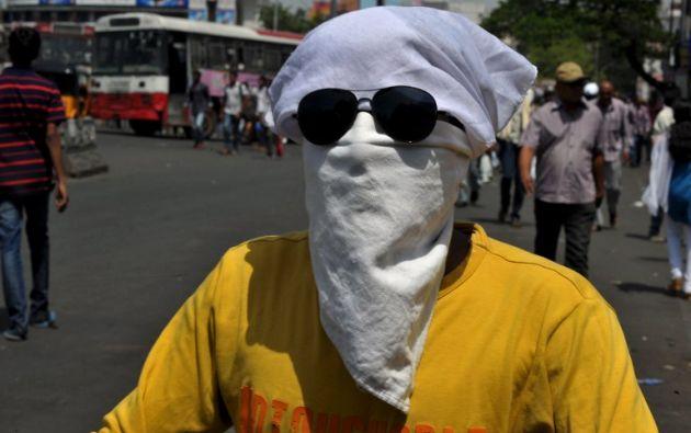 Un hombre indio cubre su rostro mientars va en un scooter bajo el sol caliente en Hyderabad el 26 de mayo de 2015. NOAH SEELAM / AFP