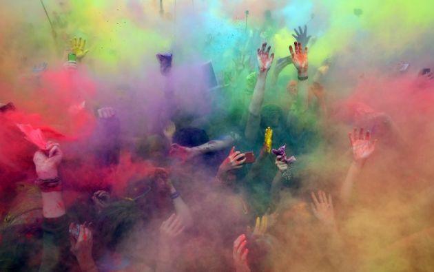 La gente disfruta ser rociada con polvo de color durante un festival anual de los colores en Moscú el 23 de mayo de 2015. AFP PHOTO / DMITRY SEREBRYAKÓV