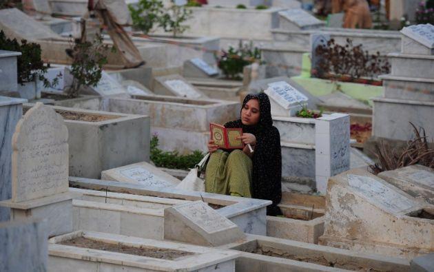 Una musulmán paquistaní recita el Corán junto a las tumbas de los familiares para marcar Shab -e- Barat o la noche del perdón. ASIF HASSAN / AFP