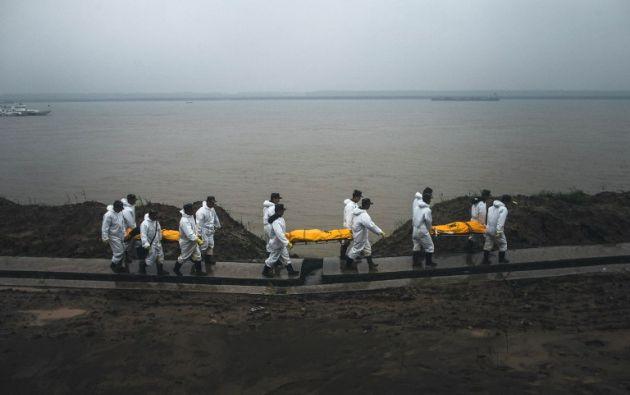 Foto tomada el 03 de junio 2015 muestra socorristas que llevan los cuerpos de las víctimas del crucero chino volcado caminando en la orilla del río en Jianli, provincia de Hubei, centro de China. STR / AFP