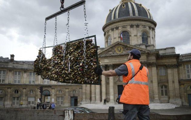 """Un trabajador retira los """"candados del amor""""  unidos en las barandillas del  Pont des Arts el 1 de junio de 2015 en de París. Iniciado por turistas en el 2008S. STEPHANE DE SAKUTIN / AFP"""