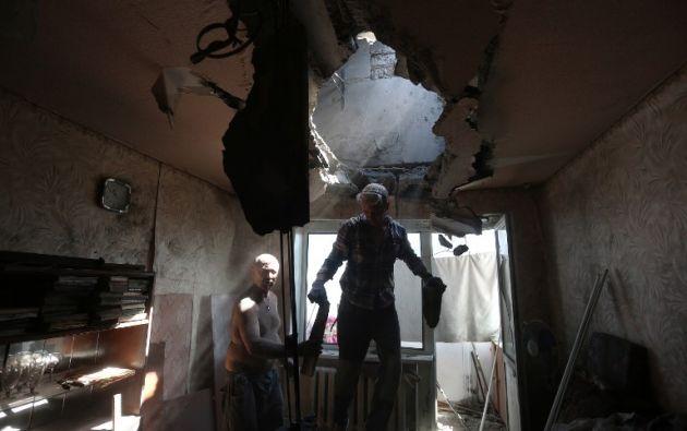 Residentes reparan el techo de un piso dañado en el bombardeo entre las fuerzas ucranianas y los separatistas prorusos en la ciudad ucraniana oriental de Horlivka en la región de Donetsk. ALEKSEY FILIPPOV / AFP