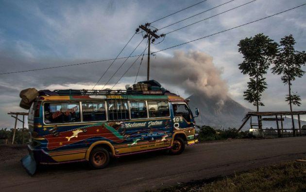 Últimas unidades de autobuses públicos que van cerca del volcán Monte Sinabung (fondo), ya que arroja cenizas volcánicas en el aire. SUTANTA ADITYA / AFP
