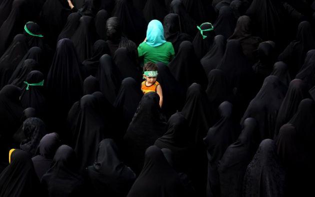 Un niño observa mientras los dolientes iraníes asisten al funeral los tres miembros de la Guardia Revolucionaria de la República Islámica supuestamente muertos en Siria. ATTA KENARE / AFP